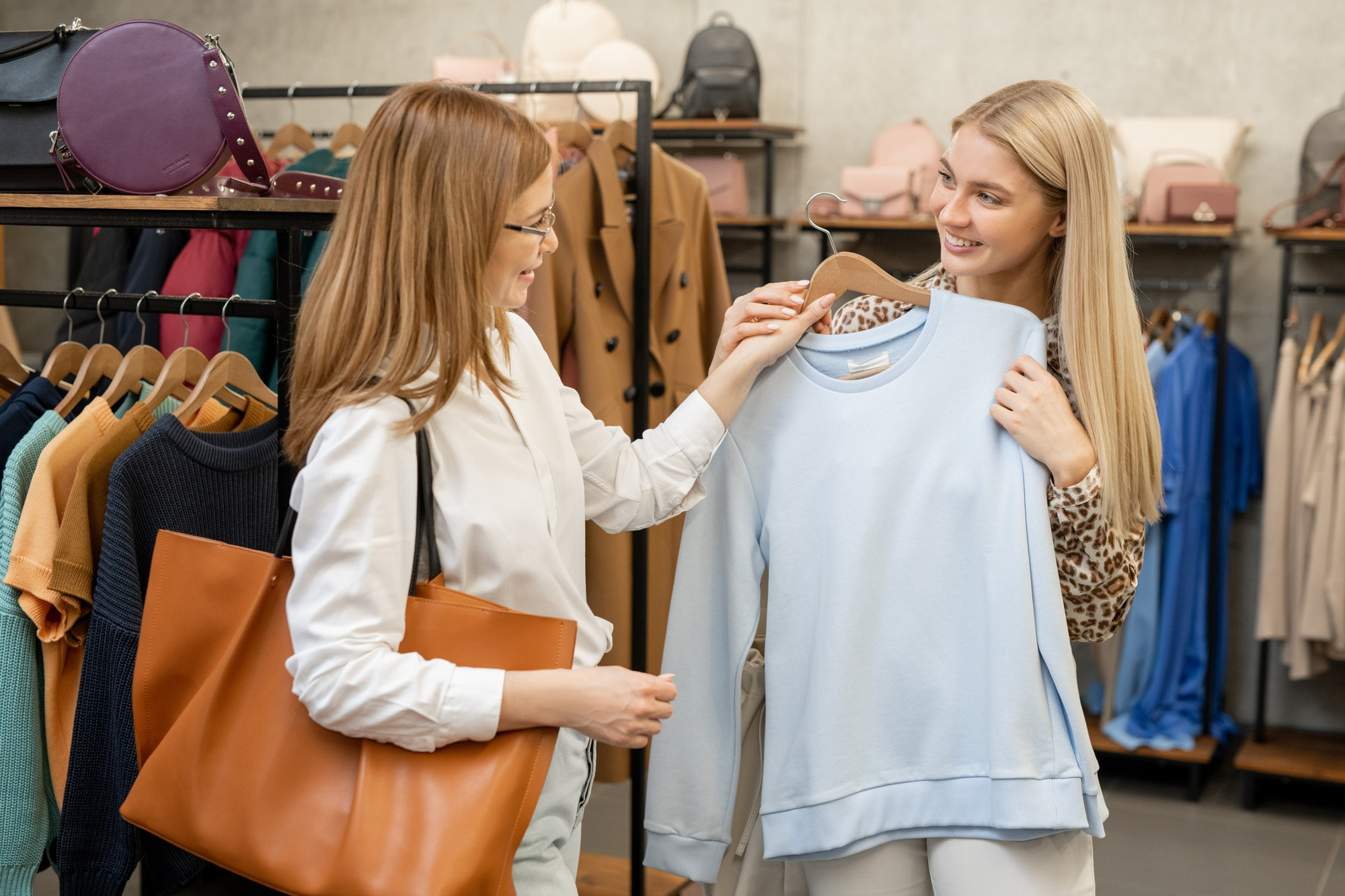 Young blond female consulting with mother while showing her white sweatshirt